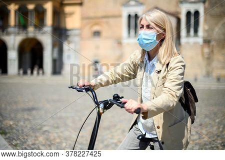 Mature woman wearing face medical mask while riding a bicycle during quarantine outdoors