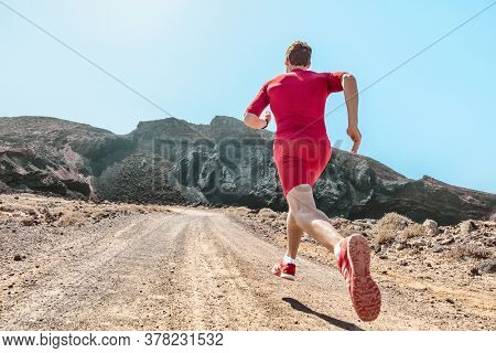Trail run runner athlete sprinting on rocks path outdoors in mountains landscape. Fit man training in volcanic field for marathon race. Male in compression shorts sportswear clothes running shoes.