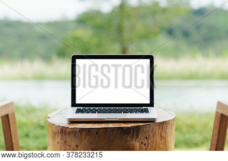 Laptop With Blank Screen On Empty Space  On Table With Green Natural Background