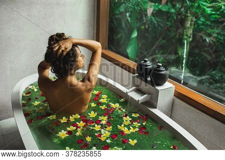 Beautiful Young Woman Enjoying In Spa, View From Behind. Luxury Stone Bath Tub With Jungle View In W