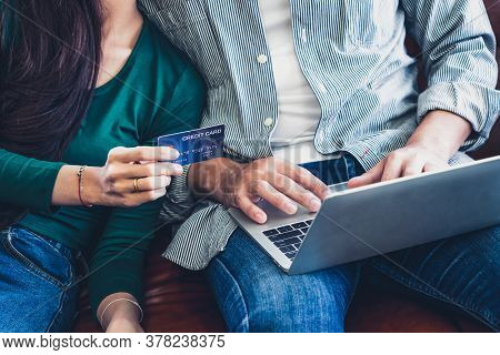 Young Couple Use Credit Card For Online Shopping On Internet Website At Home. Number On The Credit C
