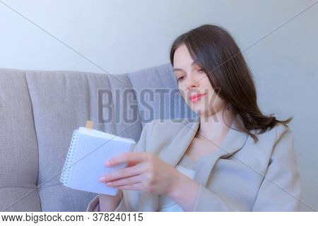 Brunette Businesswoman Writing Something In Paper Notebook Sitting On Couch At Home. Woman Is Thinki