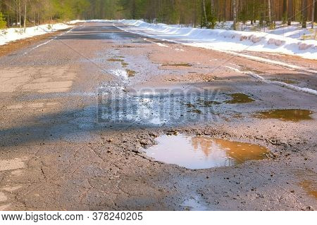 Destroyed Broken Asphalt Country Road With Holes, Melting Snow And Puddles Early Spring. Old Village