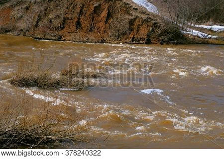 Waterfall On River Near Mountain At Spring With Naked Bushes, Flood, High Water. Abandoned Hydroelec