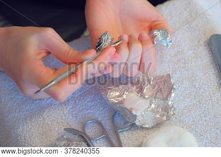 Woman Removing Shellac From Nails Using Pusher, Making Manicure At Home For Herself. Removing Gel Po
