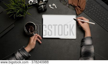 Female Hand Using Tablet With Stylus Pen And Holding Coffee Cup On Dark Office Desk, Clipping Path.