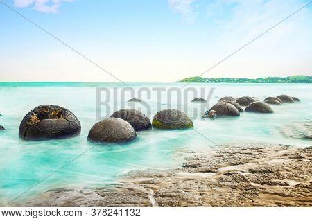 Spheric Moeraki Boulders on the Koekohe beach, Eastern coast of New Zealand.  Long time exposure - see is blurred