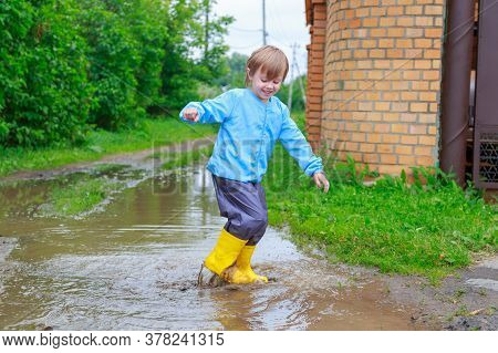.child In Rubber Boots And Raincoat Playing In A Puddle