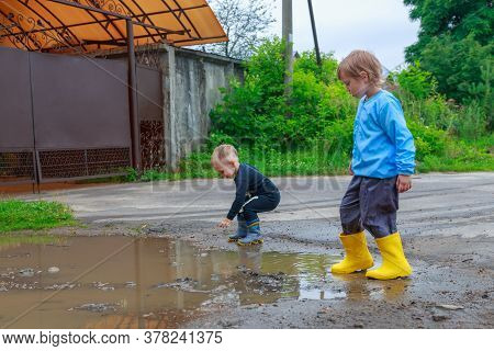 .children In Rubber Boots And Raincoats Play In A Puddle