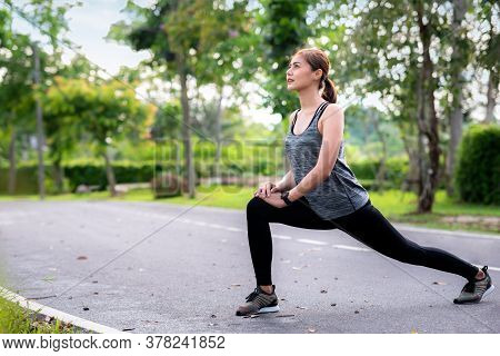 Young Asian Woman Runner Doing Stretch Exercise Stretching Legs. She Athlete Running At Garden . Spo