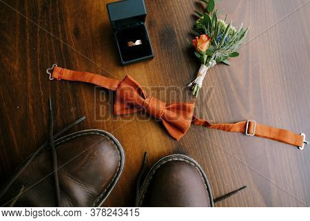 Close-up Of Grooms Bow Tie With Boutonniere, Mens Engagement Ring In A Box And Mens Boots On Brown F
