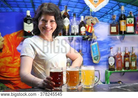The Girl Is A Bartender And Three Beers. Glasses With Different Sorts Of Craft Beer. Red, Bronze And