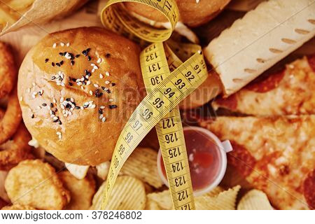 Unhealthy And Junk Food. Different Types Of Fastfood And Snacks On Table With Measuring Tape