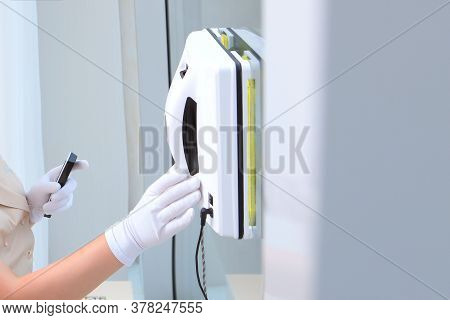 The Maid Puts The Robot On The Glass In The Window. Robot-window-cleaner. Cleaning At The Hotel Or A