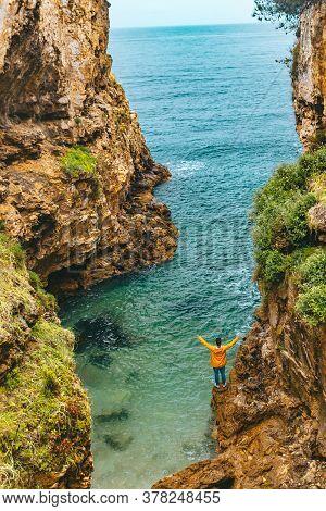 Man In Yellow Raincoat Hiking To Sea Beach At Canyon