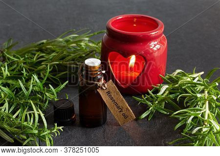 Bottle Of Rosemary Essential Oil, Candle And Fresh Rosemary Branch On Black Background.