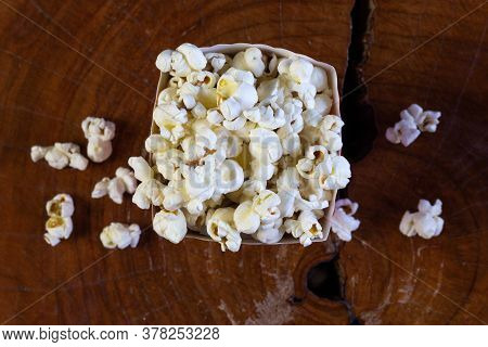 Popcorn In Striped Retro Red And White Cardboard Box For Cinema On Wooden Table