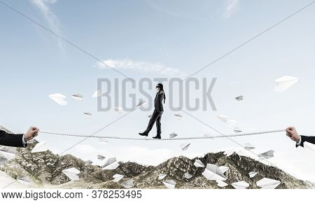 Businessman Walking Blindfolded On Rope Among Flying Paper Planes And Above High Mountains As Symbol