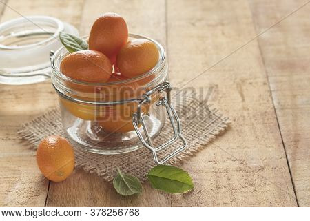 Glass Jar With Yummy Kumquat Fruits On Wooden Table, Space For Your Text