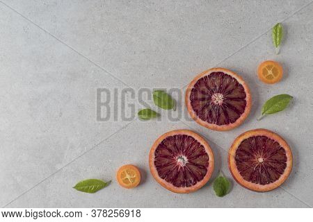 Flat Lay Composition With Sliced Blood Oranges And Kumquat Fruits On Grey Background, Copy Space Tex