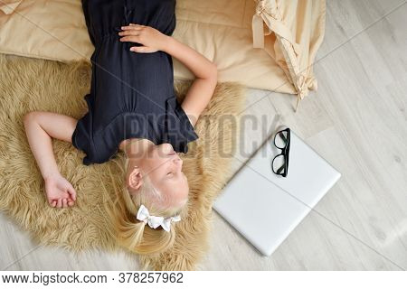 Little Girl Fell Asleep On The Floor In Her Room Next To A Laptop