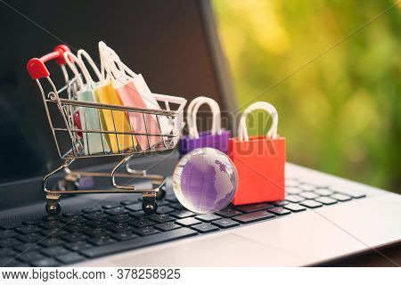 Paper Shopping Bags In A Trolley Or Shopping Cart On Keyboard. Concept About Online Shopping That Cu