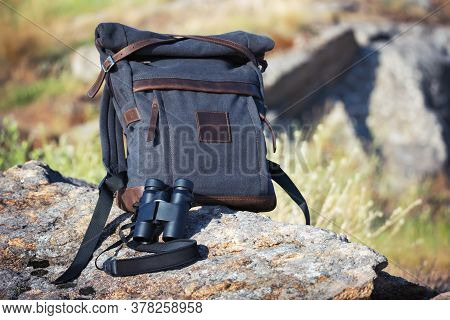 Travel Backpack With Binoculars On Rocks Nature Background