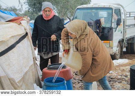 Aleppo, Syria, February 15, 2017 A Refugee Girl Pours Water In A Bucket In The Snow, Inside A Refuge