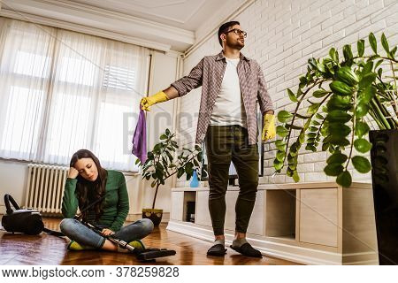 Woman Is Lazy. Man Is Telling Her To Continue Cleaning Their Apartment.
