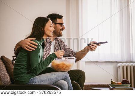 Couple Is Relaxing At Home. They Are Watching Tv.