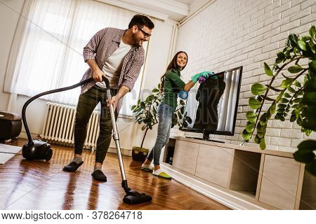 Young Happy Couple Is Cleaning Their Apartment.