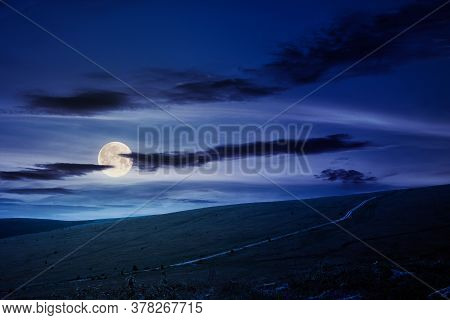 Travel Carpathian Mountains In Summer At Night. Road Through Green Grassy Meadows In The Distance In