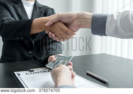 Photo Of Businessmen Shakes Hands And Dollar Note, Sign A Contract To Bribe Corruption In The Compan