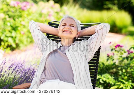 old age, retirement and people concept - happy smiling senior woman resting on chair at summer garden