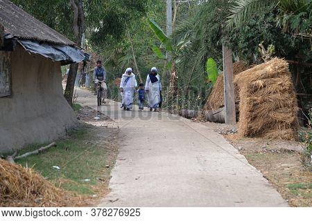 CHUNAKHALI, INDIA - FEBRUARY 26, 2020: Missionaries of Charity - Mother Teresa nuns walk with child in Chunakhali, West Bengal, India