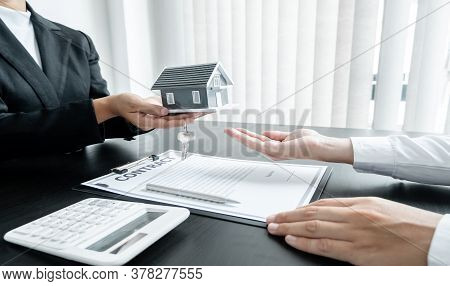 Real Estate Agent Broker Hand Over The House Key And Home To The New Owner After Completing The Sign
