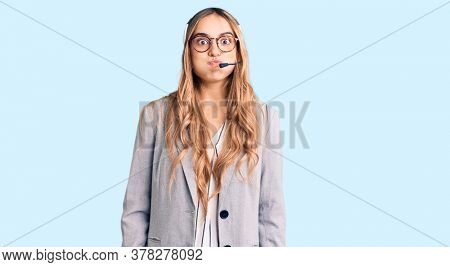 Young beautiful blonde woman wearing call center agent headset puffing cheeks with funny face. mouth inflated with air, crazy expression.