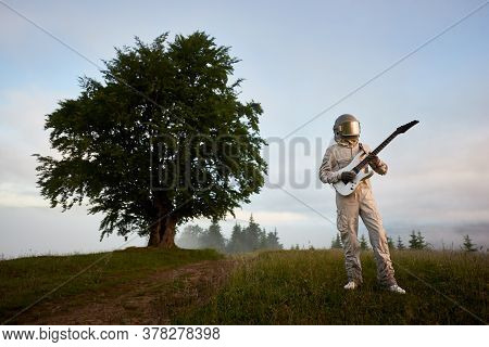 Astronaut Guitarist In Space Suit And Helmet With Musical Instrument Playing Guitar, Standing In Hil