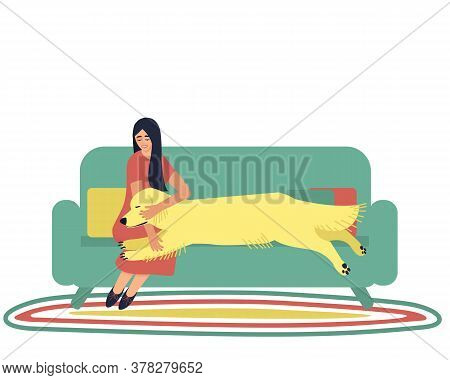 The Woman Is Sitting On The Couch Hugging A Dog. Dog Handler Hugs His Golden Labrador Dog. A Strong