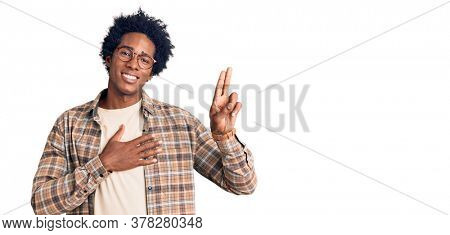 Handsome african american man with afro hair wearing casual clothes and glasses smiling swearing with hand on chest and fingers up, making a loyalty promise oath