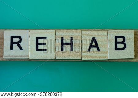 Gray Word Rehab Made Of Wooden Square Letters On Green Background