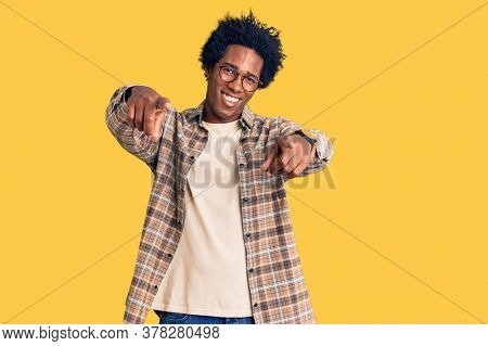 Handsome african american man with afro hair wearing casual clothes and glasses pointing to you and the camera with fingers, smiling positive and cheerful