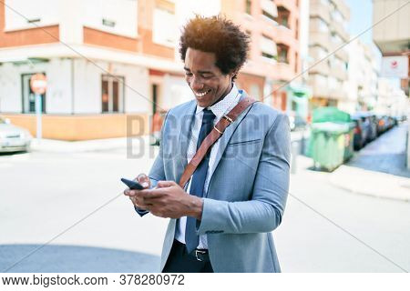 Young african american businessman wearing suit smiling happy. Standing with smile on face using smartphone at town street.