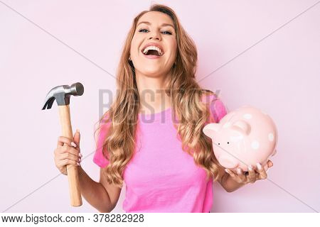 Young caucasian woman with blond hair holding piggy bank and hammer smiling and laughing hard out loud because funny crazy joke.