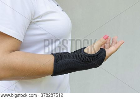 Black Wrist Brace Or Corset Is Worn On Women's Hand For Treatment Of Carpal Tunnel Syndrome Or Media