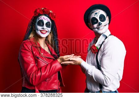 Couple wearing day of the dead costume over red pointing aside with hands open palms showing copy space, presenting advertisement smiling excited happy