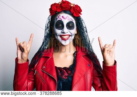 Woman wearing day of the dead costume doing rock and roll gesture with fingers smiling and laughing hard out loud because funny crazy joke.