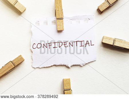 White Paper With Text Confidential With Clothespins On White Background