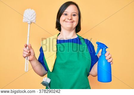 Brunette woman with down syndrome wearing apron holding scourer and toilet brush smiling with a happy and cool smile on face. showing teeth.