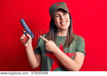 Young beautiful brunette woman wearing t-shirt with red star communist symbol holding gun smiling happy pointing with hand and finger